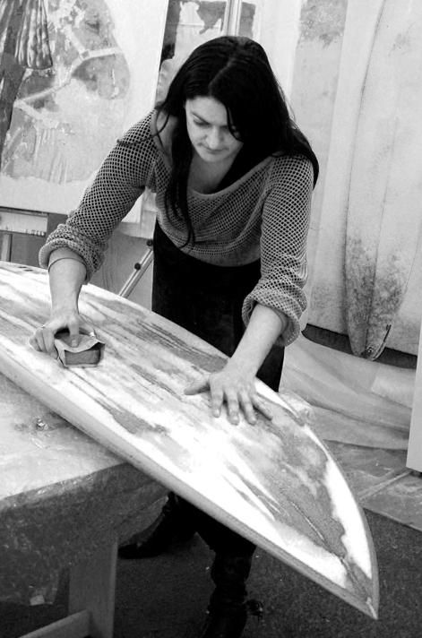 kristine khana aka khanage working on a surfboard